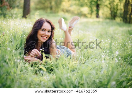 sunny summer day, a beautiful young girl lying on the grass