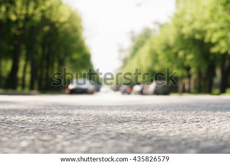 sunny summer day small street in town camera close to the ground - stock photo