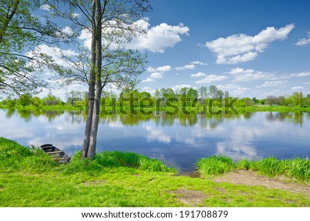 Sunny summer landscape. Trees and Boat at riverbank. Valley of The Narew River, Poland. - stock photo