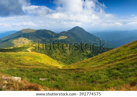 Sunny summer scene in the mountains. View of beautiful panoramic landscape of a green hills. - stock photo