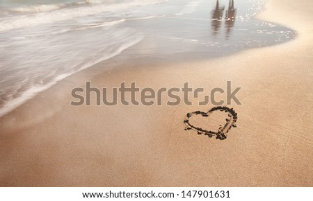 Sunny summer sea love sign on sand with wave and couple (reflection). Neutral densitiy filter used to make blurry waves. - stock photo