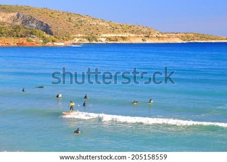 Sunny surf beach on the shores of the Aegean sea, Vouliagmeni, Greece - stock photo