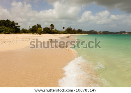 Sunny Tropical Caribbean Beach with Blue Cloudy Sky and Copy Space - stock photo