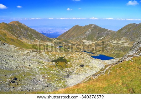 Sunny valley with a lake and a hut surrounded by green summits, Fagaras, Romania - stock photo