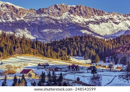 Sunny winter alpine scenery with small Romanian village in the valley of Bucegi massif, Fundata village, Brasov county, Romania. - stock photo