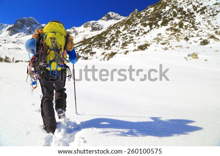 Sunny winter day with backpacker casting a shadow on snow covered mountain - stock photo