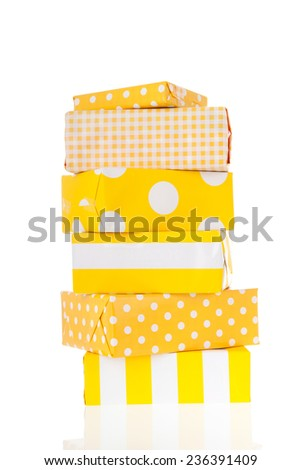 Sunny yellow wrapped gifts stacked and isolated over white background - stock photo