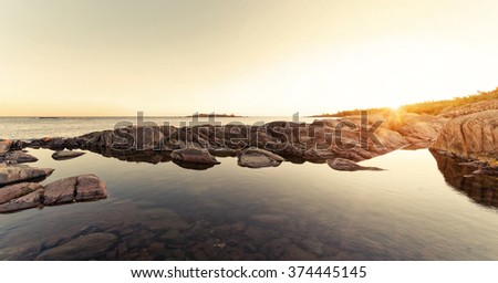 Sunrays over rocky coast during early morning. Grisslehamn, Sweden - stock photo