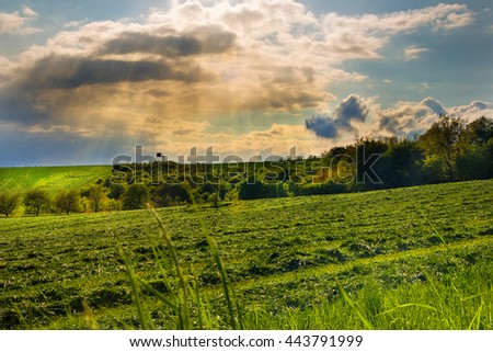 Sunrays shining through clouds and field with cut grass. Moravian landscape Visky.