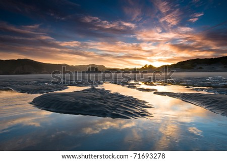 Sunrise above beach with reflection on incoming tide - stock photo
