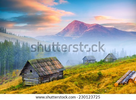 Sunrise above the high mountain foggy valley with old wooden houses on a hill in a mountain forest.  - stock photo
