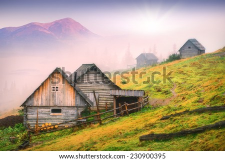 Sunrise above the nature wooden houses in a Carpathian mountains with highest mountain of Ukraine, Goverla. Early misty morning, beginning of new day. - stock photo