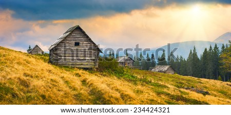 Sunrise above the nature wooden Ukrainian houses in a Carpathian mountains. Early misty morning, beginning of new day. - stock photo