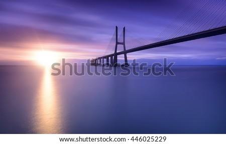 Sunrise and bridge over tagus river in Lisbon Portugal - stock photo