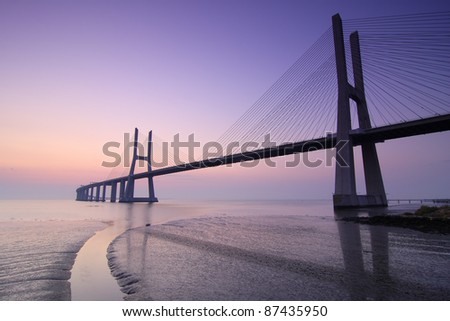 Sunrise and bridge over tagus river in Lisbon Portugal - stock photo