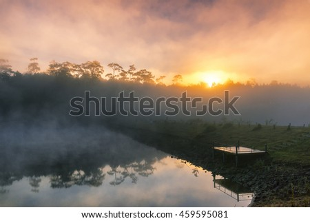 Sunrise and mist in beautiful lake with morning fog - stock photo
