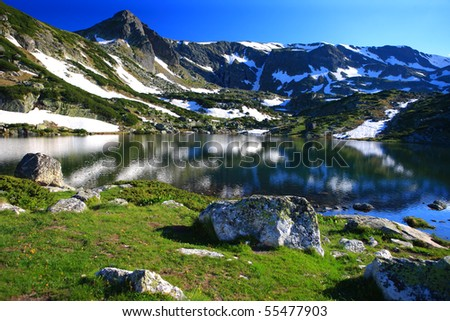 sunrise and peak reflection on the lake - stock photo