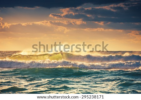 Sunrise and shining waves in ocean - stock photo