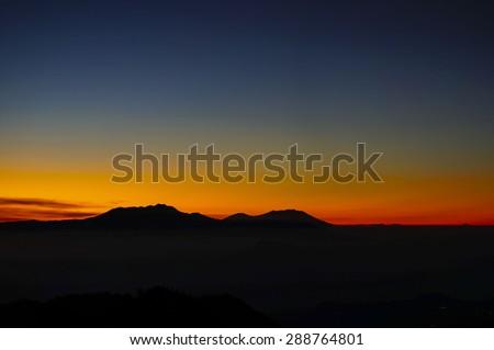Sunrise and silhouette of Volcanoes in Bromo Tengger Semeru National Park - stock photo