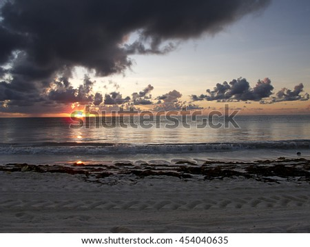Sunrise at a beach on a cloudy day - stock photo