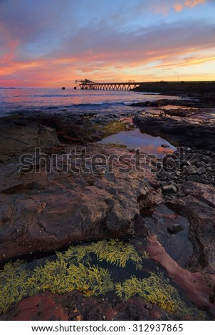 Sunrise at Bass Point Shell Cove south coast Australia with gravel loader in the far off distance.   - stock photo