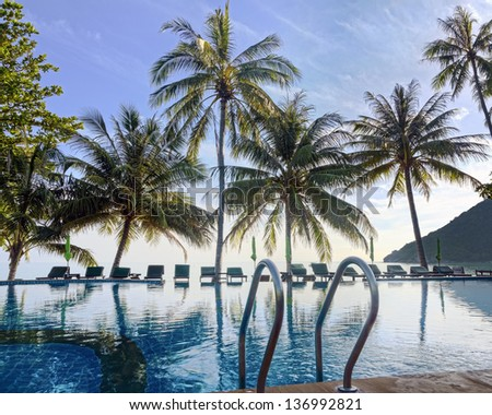 Sunrise at beach about of pool on resort in the tropics. Silhouettes of palm trees - stock photo
