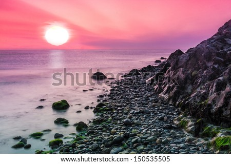 Sunrise at Bray Head in the little fisherman's town of Bray in Ireland. When lucky the sun is as big as can be and you can enjoy this scene sitting on the beach with a loved one or just by yourself. - stock photo