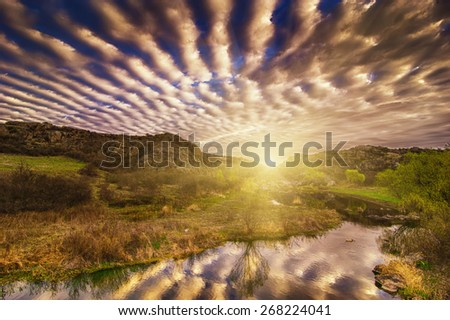 Sunrise at canyon with river, sun and dramatic sky with reflection - stock photo