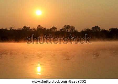 Sunrise at Kavango river whit mist on the water surface, Caprivi region. Namibia - stock photo