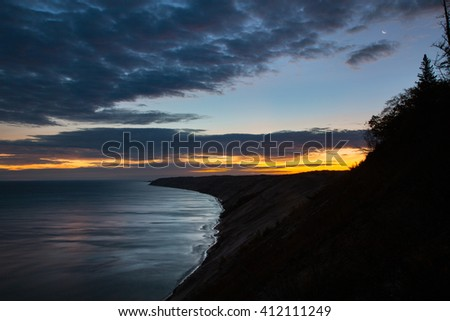 Sunrise at Lake Superior. The moon still hangs overhead. Grand Sable Dunes sits amid Pictured Rocks National Lakeshore in the Upper Peninsula of Michigan - stock photo