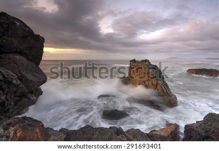 Sunrise at Lighthouse beach a soft golden glow warms the side of the rocks and highlights the water and clouds in a subtle way - stock photo