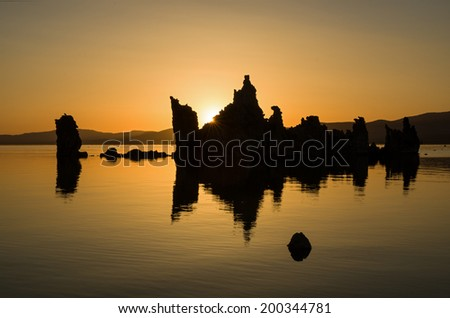 sunrise at Mono Lake over tufa towers with golden sky and reflection in water - stock photo