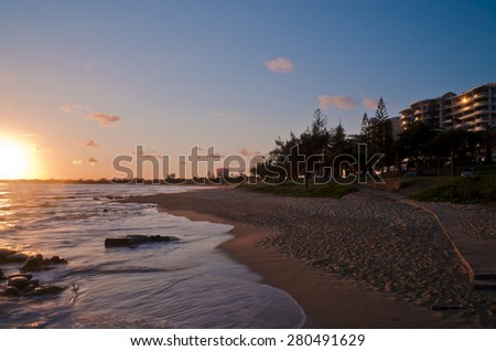 Sunrise at Mooloolaba, Queensland, Australia. Sun is rising over see and reflecting on highrise building windows. - stock photo