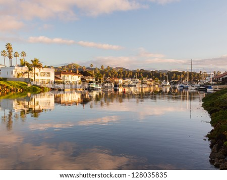 Sunrise at residential development by water in Ventura California with modern homes and yachts boats - stock photo