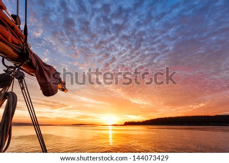 Sunrise at sea on a sailboat with a view of the sail and rigging against a beautiful pink and gold sky reflected in the water. Copy space  - stock photo