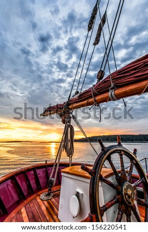 Sunrise at sea on a tall ship classic sailboat.  Close up of the wheel, boom and stern against a dramatic sky and gold sunlight reflections. Concepts: Serenity, prosperity, optimism, positive, future - stock photo