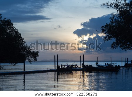 sunrise at sea  with long tail boat - stock photo