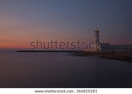 Sunrise at the mediterranean sea with the view to the lighthouse - stock photo