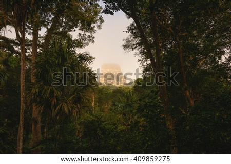 Sunrise at the Tikal temple complex just after the morning fog lifted to reveal all the structures - stock photo