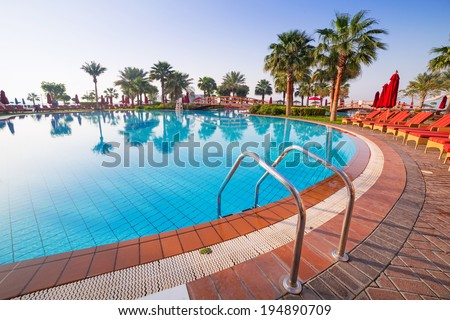 Sunrise at the tropical swimming pool - stock photo