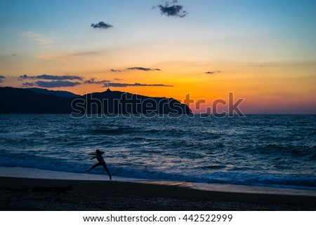 Sunrise at Tinderi beach with a girl jumping in the foreground