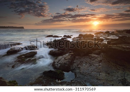 Sunrise at Warriewood beach low tide with gentle flows and pretty altocumulus clouds partiially obscure the sun, its warm winter rays highlight the waves and rocks - stock photo