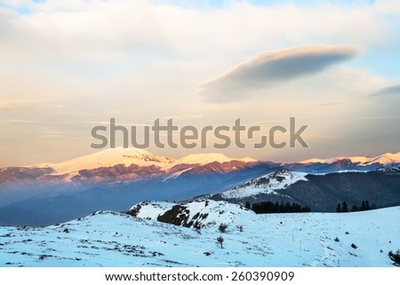 Sunrise at winter mountain with snowy peaks and clouds - stock photo