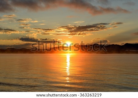 Sunrise at Yellowstone Lake - A late August morning, the sun rises over the foggy Yellowstone Lake, Yellowstone National Park, Wyoming, USA. - stock photo