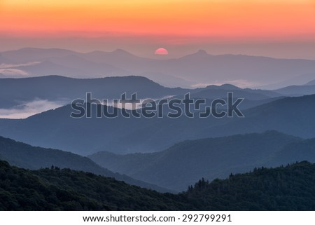 Sunrise between North Carolina's iconic Table Rock and Hawksbill mountains as seen from the Blue Ridge Parkway. - stock photo