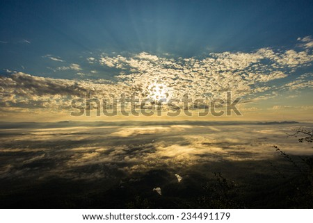 Sunrise beyond the mist in the mountain. - stock photo