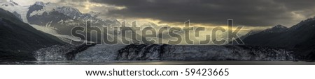 Sunrise breaking through the clouds onto a panorama of the Harvard Glacier. - stock photo
