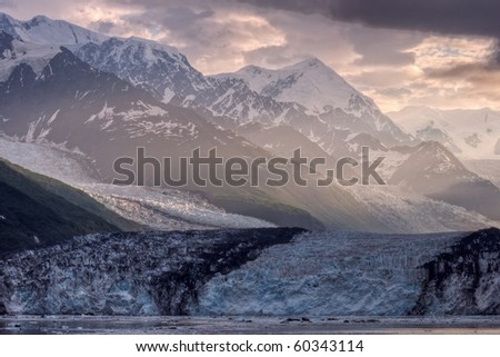Sunrise breaking through the clouds onto Harvard Glacier. - stock photo