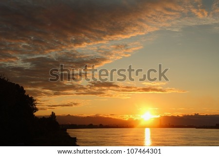 Sunrise Fraser River. Sunrise shot of the Fraser River along a stretch lined with industry. The Coast Mountains rise in the background. Vancouver, British Columbia, Canada. - stock photo