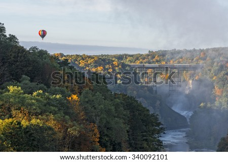 Sunrise From Inspiration Point At Letchworth State Park In New York With A Hot Air Balloon Flying Near The Railroad Trestle - stock photo